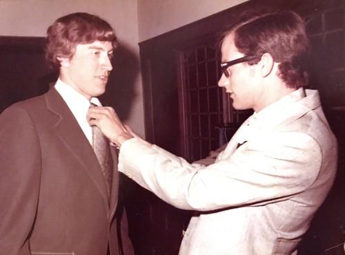 Peter adjusts Paul's tie